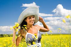 Portrait of charming girl with hat standing in the field Stock Photos