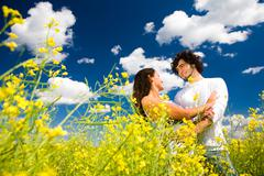 View of amorous couple in golden meadow under summer sky with clouds on it Stock Photos