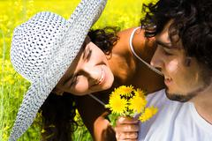close-up of smiling woman showing bunch of yellow dandelions to handsome man who - stock photo