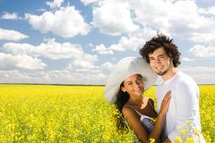 Photo of young couple standing on field and hugging each other while looking at Stock Photos