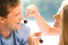 Portrait of pretty woman holding cherry with man near by Stock Photos