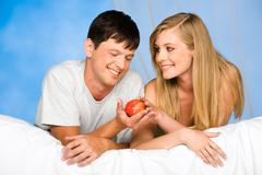 Photo of beautiful couple on bed: woman taking ripe apple from man's hand Stock Photos