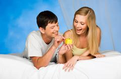 Portrait of man making a present to surprised woman at morning Stock Photos