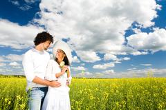 Image of happy amorous couple standing on the field and looking at each other wi Stock Photos