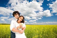Photo of amorous couple wearing white clothes standing in meadow full of yellow Stock Photos