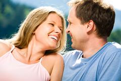 close-up of joyful woman laughing while looking at smiling man - stock photo