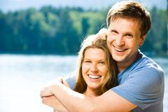 portrait of happy couple looking at camera while smiling man embracing pretty wo - stock photo