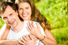 portrait of beautiful woman hugging her husband while both looking at camera wit - stock photo