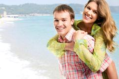 photo of young happy couple enjoying themselves at sea during holiday - stock photo