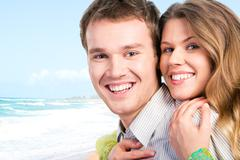 Close-up of beautiful joyful couple looking at camera on the background of sea Stock Photos
