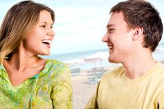portrait of two young people speaking to each other and laughing on the backgrou - stock photo