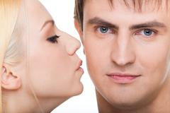 handsome guy looking at camera with pretty girl kissing him - stock photo