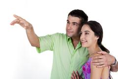 Handsome man embracing pretty woman while both looking at something over white b Stock Photos