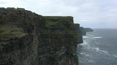 Steep walls of Cliffs of Moher pan right - Atlantic ocean + clouds Stock Footage