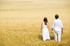image of couple holding by hands and walking along the field - stock photo