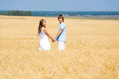 Portrait of two people standing together in wheat field Stock Photos