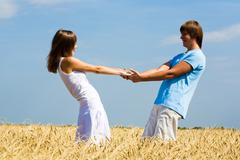 image of happy young man and woman holding each other by stretched hands while s - stock photo