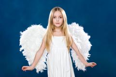 Portrait of happy angel wearing white clothing and wings over blue background Stock Photos