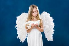 Portrait of light angel with purely white dove looking at it with love Stock Photos
