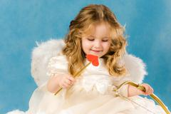 Photo of adorable female cupid holding bow Stock Photos
