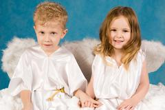 portrait of two cute children wearing white silk clothing and looking at camera - stock photo