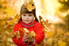 portrait of small girl catching falling leaves in autumn forest - stock photo