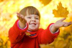 Very cheerful child having fun while tossing up yellow leaves Stock Photos