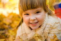 face of girlie looking at camera with cute smile while on autumnal ground - stock photo