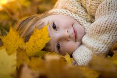 Head of girlie lying on golden leaves in autumn with peaceful expression Stock Photos