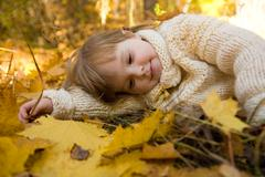 Tired girl relaxing on autumn ground covered with dry maple leaves Stock Photos
