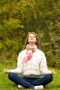 Portrait of pretty woman doing yoga exercise in the park Stock Photos