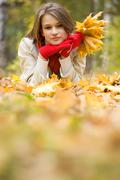 image of resting young woman lying on foliage in autumn - stock photo
