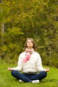 portrait of calm girl meditating outside in autumn - stock photo