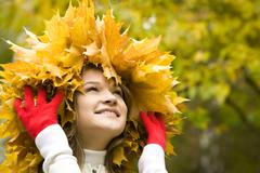 portrait of pretty girl wearing maple wreath and touching it by hands - stock photo