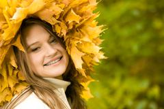 smiling girl with maple wreath looking at camera on green background - stock photo