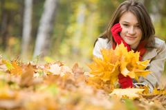 Image of pretty girl lying on ground covered with yellow dry leaves in fall Stock Photos