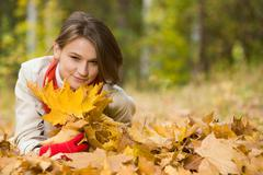 image of cute young woman lying on autumnal land in the park - stock photo