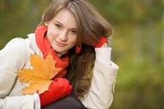 portrait of smiling pretty woman with leaf in autumnal environment - stock photo