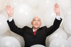 Photo of joyful man wearing suit inside balloons raising his arms Stock Photos