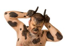 Stock Photo of portrait of painted man showing horns and looking at camera with aggressive grim