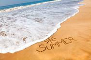 Stock Photo of the word summer written in the sand on a beach with drawing of the sun, sea b