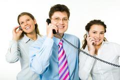 portrait of three consultants speaking on the telephones - stock photo