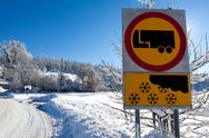 Stock Photo of traffic sign warns of snow and ice, on sunny and snowy day