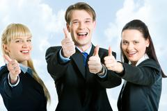 Portrait of three happy business partners holding their thumbs up on the backgro Stock Photos