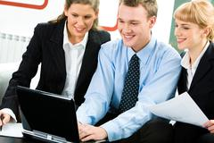 Image of successful business man between the two women typing on the laptop Stock Photos
