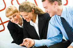 Image of business team looking at document and discussing Stock Photos