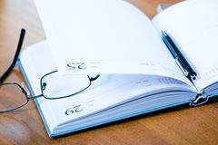 Image of glasses, notepad with pen lying on the table Stock Photos