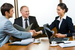Photo of business partners holding hands making a consensus Stock Photos