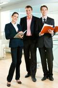 Vertical photo of business team standing in the office: confident businessman be Stock Photos