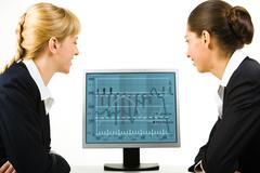 Portrait of two business ladies looking into the computer screen Stock Photos